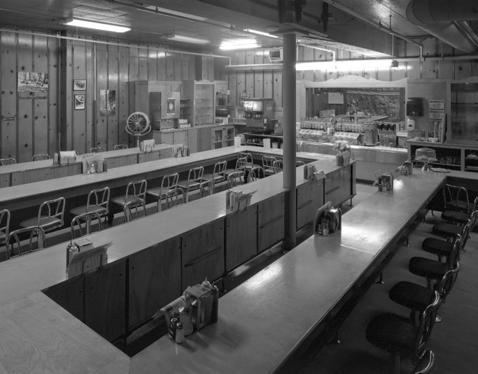 The coffee shop and lunch counter was completed about two years after construction. The post at center was added in 1954 to support the beam cracked when a flood swept through this room in 1936, shifting the whole building's structure. Marks from debris from a second flood in 1964 are still visible on the original knotty pine paneling.