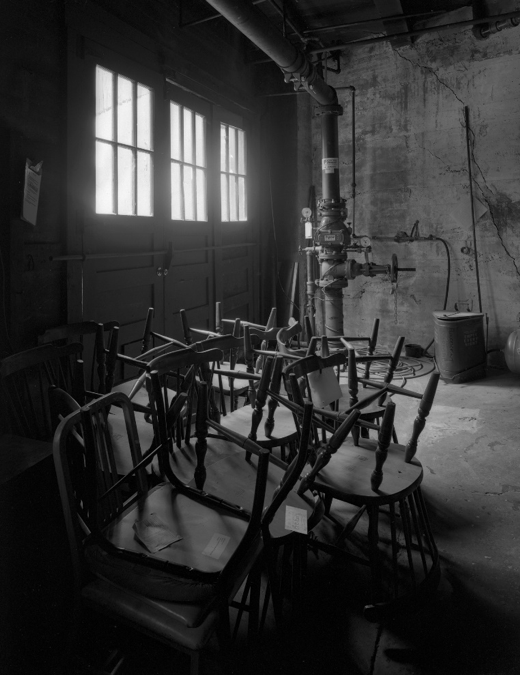 A stack of broken and unused chairs sits in the boiler room. This photograph was a two-and-a-half minute long exposure made with available light.