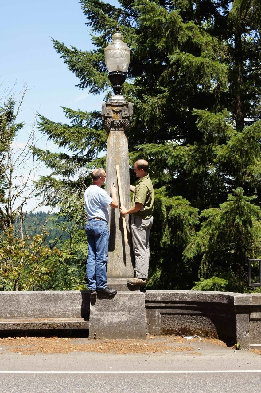"Chris Bell (right), with bridge preservation engineer, Mats Halvordson, evaluating what Chris believes is Pacific Northwest take on the Corinthian Order, ""The Pineconian."" They recorded and subsequently replicated this light post to replace ones removed during WWII on a bridge near Crater Lake. A free signed ODOT Historic Bridge Field Guide (at the San Antonio Conference) to the first VAN reader who can identify the location. Photo courtesy of Chris Bell."